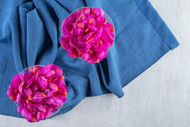 Fiori viola freschi in un bicchiere su un pezzo di tessuto, sul tavolo bianco.