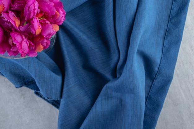 白いテーブルの上に、一枚の布の上にガラスの新鮮な紫色の花。