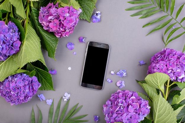 灰色の表面にスマートフォンと緑の葉を持つ新鮮な紫色のアジサイ