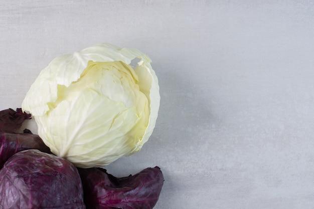 Cavoli viola e bianchi freschi sulla superficie di pietra. foto di alta qualità