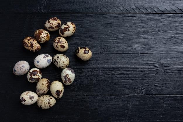 Uova di quaglia fresche sulla superficie di legno scuro.