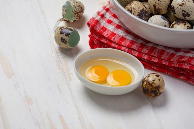 Fresh quail eggs on the white wooden surface.