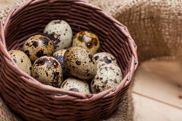 Fresh quail eggs at wooden plate closeup
