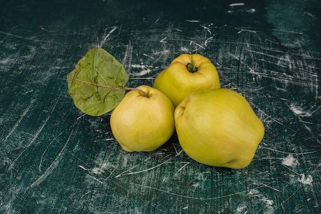 Свежие фрукты айвы на мраморном столе