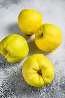 白いテーブルの上の新鮮なマルメロの果実。白色の背景。上面図。