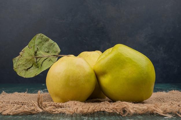Свежие фрукты айвы на шерстяной ткани