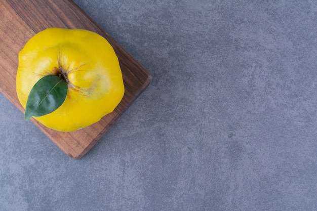 Fresh quinces on cutting board on the dark surface