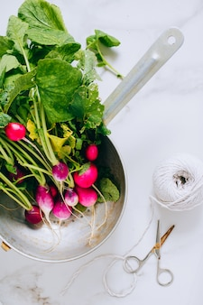 Fresh radish bunch in silver colander on marble