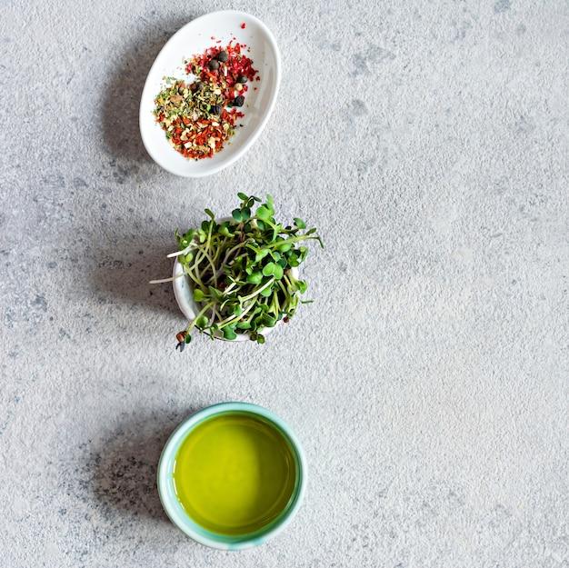 회색 배경에 올리브 오일과 후추 믹스가 든 그릇에 신선한 무 녹색 채소 건강한 생활 방식 개념 비건 음식 성장하는 콩나물 샐러드 드레싱