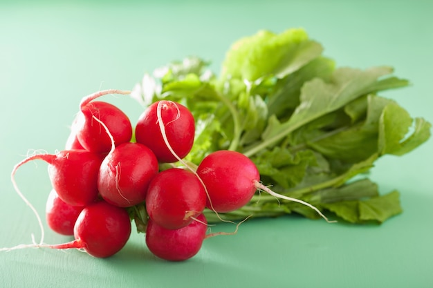 Fresh radish with leaves over green table
