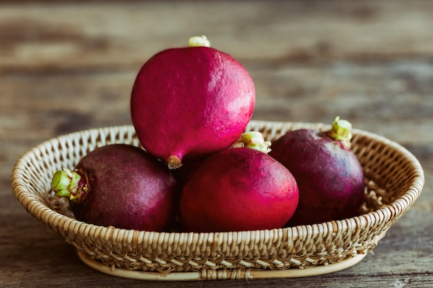 Fresh radish in wood basket put on wooden table