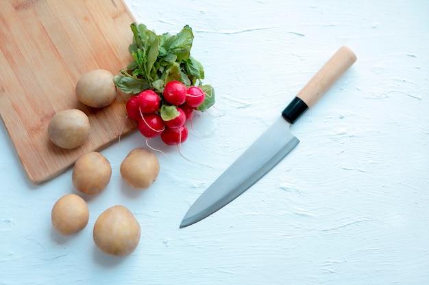 Свежий редис и нож на белом фоне и старая деревянная разделочная доска