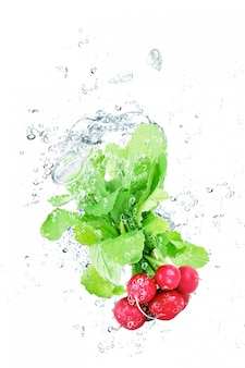 Fresh radishes falling in water