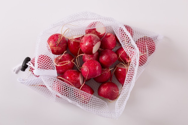 Fresh radishes in reusable packing net isolated on white background