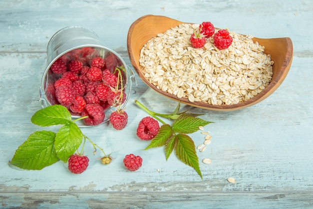 Fresh raspberries in a bucket and oat flakes in a wooden bowl on a rustic wooden background. healthy diet, vegetarian concept.