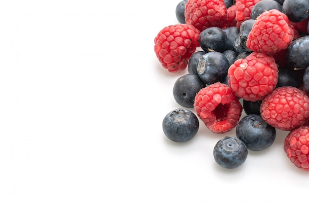Fresh raspberries and fresh blueberries on white background