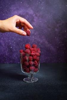 紫色の背景にあるガラスの新鮮なラズベリー。女性の手はガラスからラズベリーを取ります。正面図。垂直。コピースペース