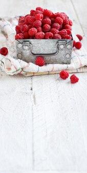 金属製の箱に入った新鮮なラズベリーをクローズアップ Premium写真