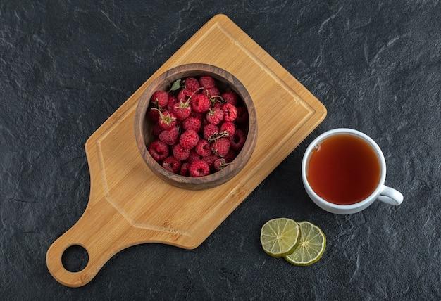 Свежая малина на деревянной доске с чаем и лимоном.