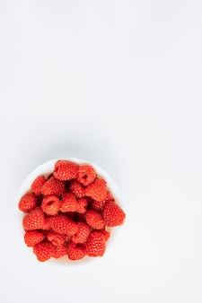 Fresh raspberries in a white bowl on a white background. flat lay.