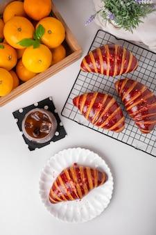신선한 오렌지와 블랙 커피를 곁들인 하얀 접시에 신선한 라즈베리 크루아상이 아침에 제공됩니다.