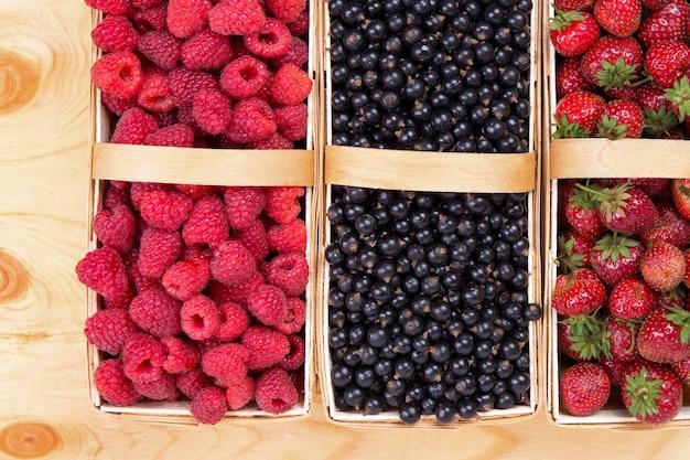 Свежие ягоды малины и смородины и клубника в корзинах на деревянных фоне