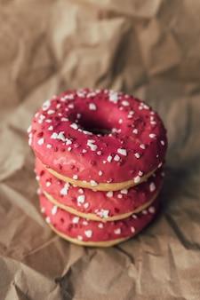 しわくちゃのクラフト紙に新鮮なラズベリードーナツ。高品質の写真