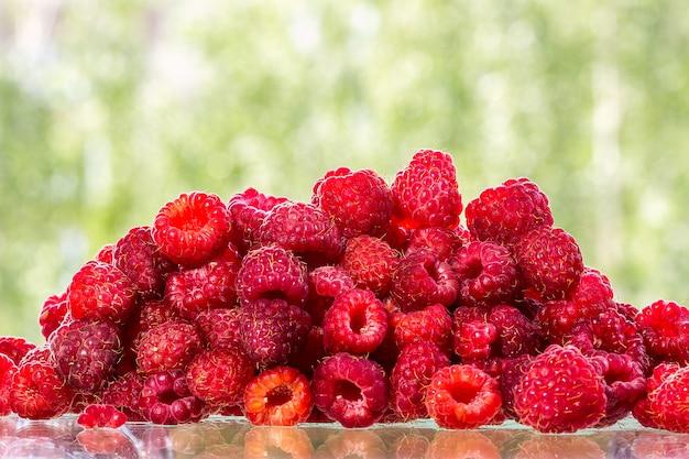 Fresh raspberry fruits on a glass table