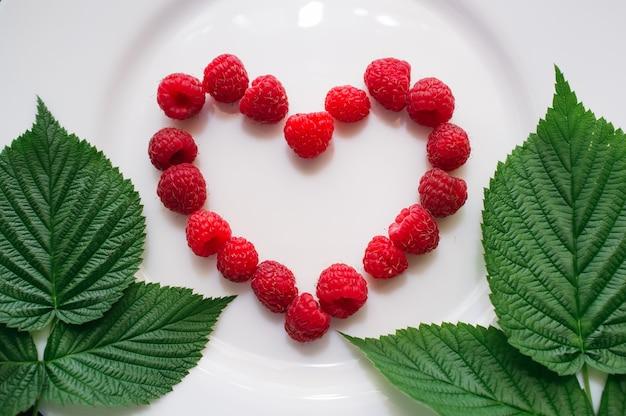 녹색 잎 장식과 흰색 접시에 신선한 라즈베리 심장 모양