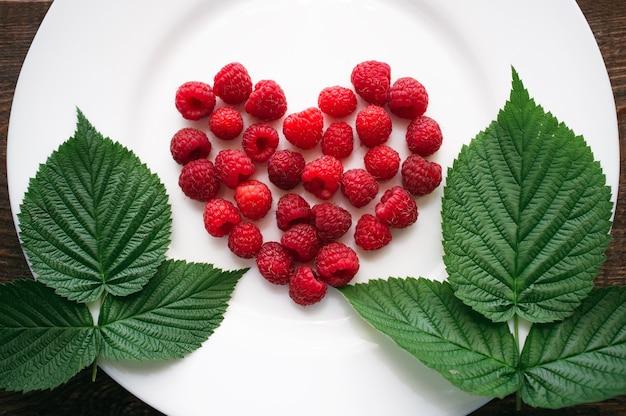Свежая малина в форме сердца с листьями на белой тарелке