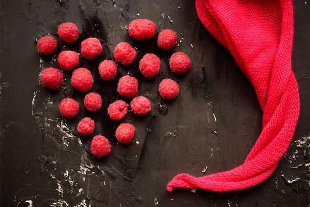 Свежая малина с розовой салфеткой на черном фоне. красное сердце - день святого валентина и дружба