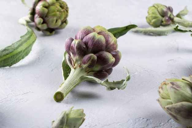 Fresh  raw artichokes on grey background. ripe organic artichoke  pattern
