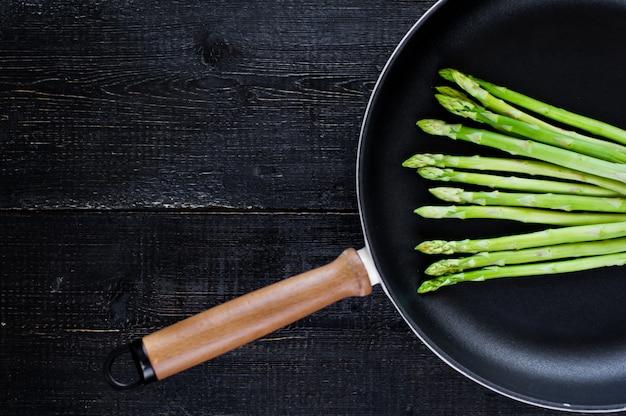Fresh raw asparagus in a pan.