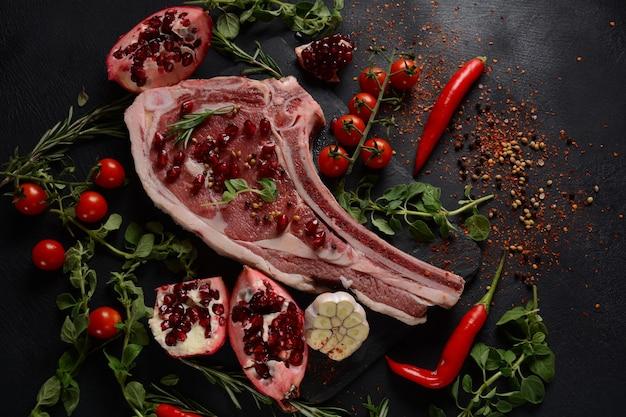 Fresh raw beef bone rib steak on black board with herbs and spices