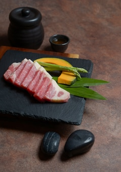 Fresh raw beef brisket slice with pumpkin pieces and asparagus on the black dish rock ,menu set.