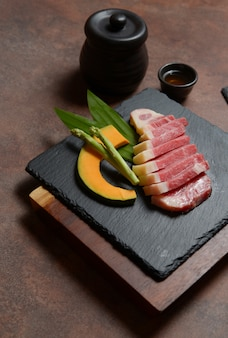 Fresh raw beef brisket slice with pumpkin pieces and asparagus on the black dish rock