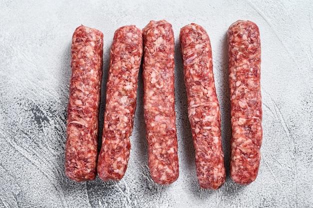 新鮮な生の牛肉のケバブソーセージ。白色の背景。上面図。