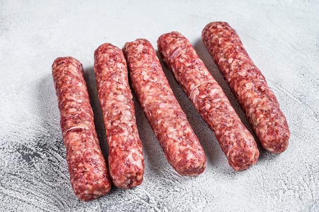 Шашлык из свежей сырой говядины, колбасы.