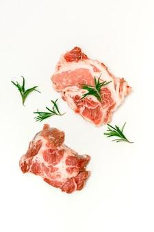 白い背景、コピースペース、自宅での料理、上面図で分離されたローズマリーと新鮮な生の牛肉ステーキ。