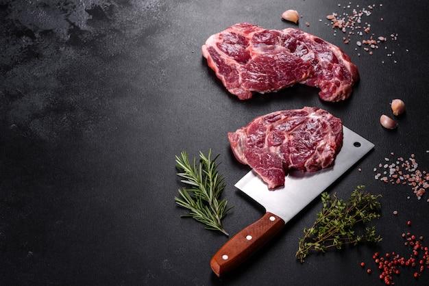 Свежее сырое мясо говядины для приготовления вкусного сочного стейка с добавлением специй и зелени. приготовление мяса на гриле