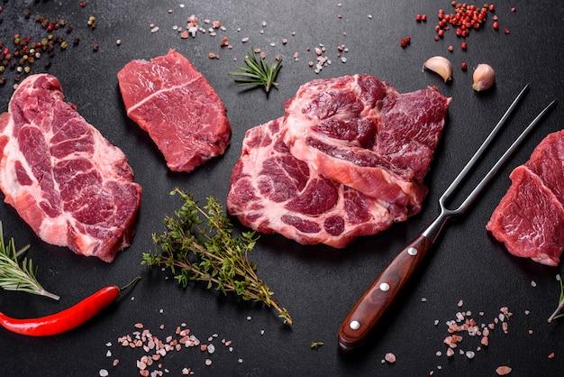 Свежее сырое мясо говядины для приготовления вкусного сочного стейка со специями и зеленью