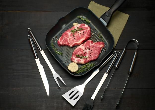 Свежие сырые стейки из говядины или свинины на сковороде