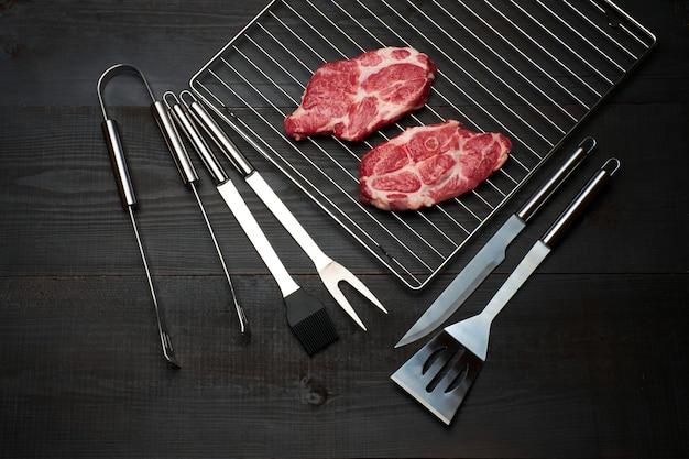 Свежие сырые стейки из говядины или свинины на решетке гриля