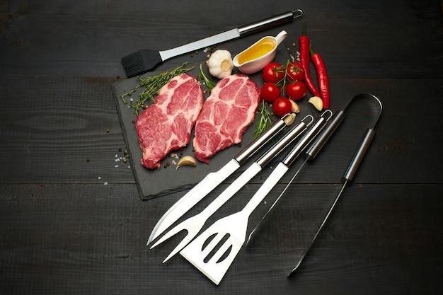Свежие сырые стейки из говядины или свинины на сервировочной доске для резки камня