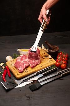Свежие сырые стейки из говядины или свинины на деревянной разделочной доске