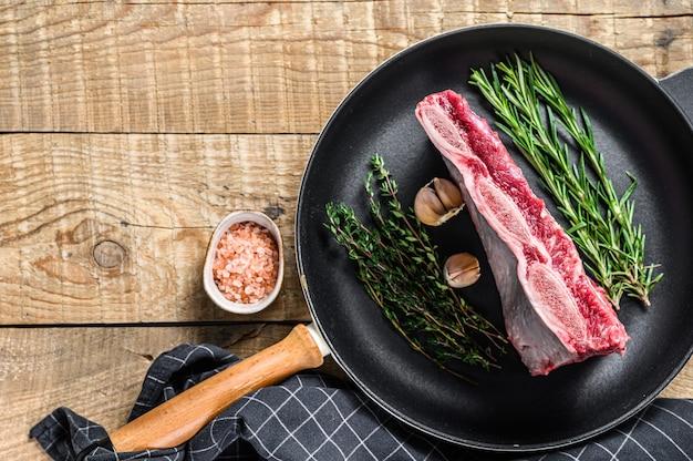 허브와 함께 냄비에 신선한 원시 쇠고기 갈비 고기. 나무 배경입니다. 평면도. 공간을 복사하십시오.
