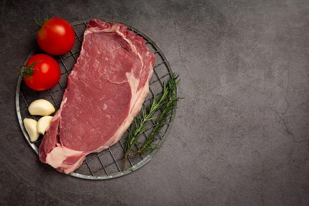 Bistecca di manzo cruda fresca sulla superficie scura.
