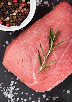 Свежий сырой говяжий стейк на каменной доске с перцем на черном фоне