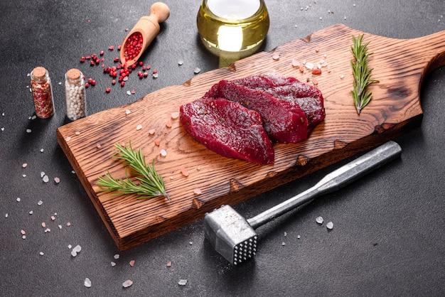 Fresh raw beef steak mignon, with salt, peppercorns, thyme, tomatoes. raw fresh marbled meat steak and seasonings