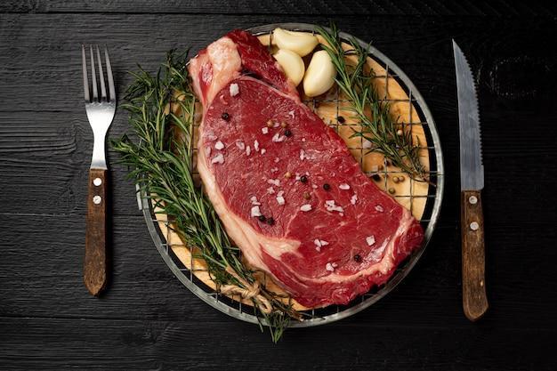 Свежий сырой стейк из говядины на темной поверхности.